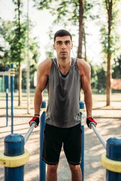 Man doing exercise on parallel bars, front view
