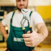 Repairman in uniform holds wrench, handyman