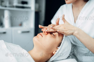 Beautician rubs the cream on female patient face