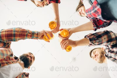 Friends clink bottles with beer, bottom view