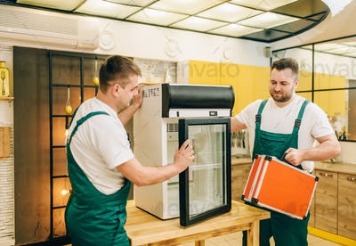 Male workers in uniform repair refrigerator