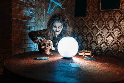 Scary witch with human skull over a crystal ball