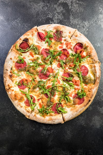 Pepperoni pizza with fresh arugula