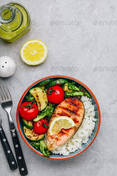 Grilled salmon steak with and rice, zucchini, broccoli, tomato .