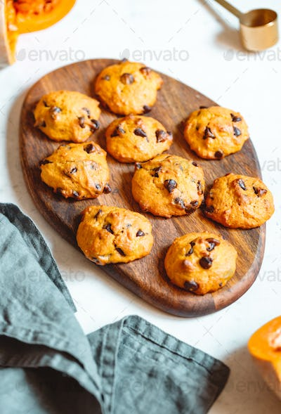 Pumpkin cookies with chocolate chips made from cake mix on a wooden tray.