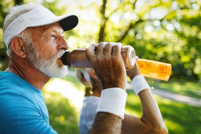 Hydrating. Sporty senior person drinking water in a park