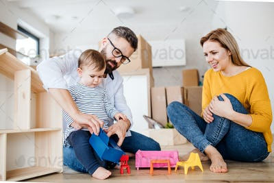 A portrait of young family with a toddler girl moving in new home, playing.