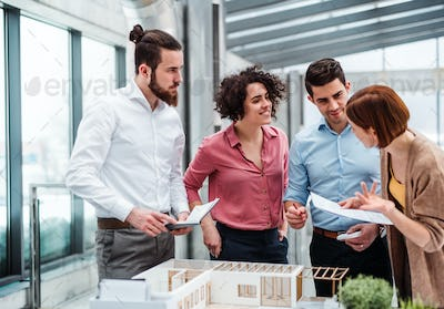 Group of young architects with model of a house working in office, talking.