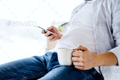 A midsection of man with smartphone and coffee sitting indoors, text messaging.