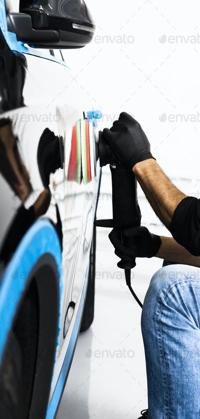 Buffing and polishing car. Car detailing. Man holds a polisher in the hand and polishes the car
