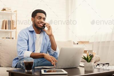 Smiling african-american guy in headphones looking at laptop