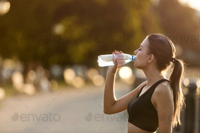 Active sporty woman drinking water from bottle after training