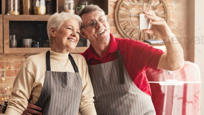Senior couple taking selfie on smartphone in kitchen