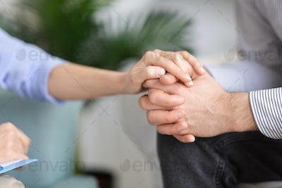 Woman holding man's hand in support gesture