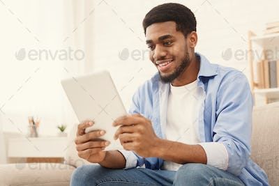 Young millennial guy using digital tablet at home