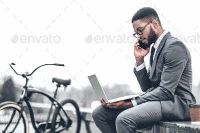 Always in touch. Businessman with bicycle working on laptop