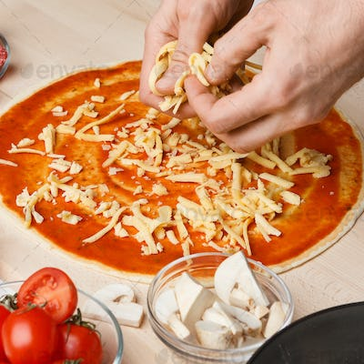 Pizzaiolo adding grated cheese to pizza base