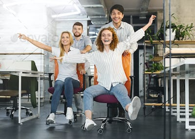 Happy colleagues having fun at workplace, making office chair race
