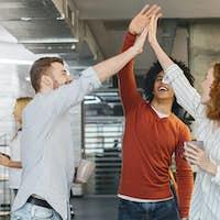 Happy coworkers having fun, giving high five during coffee break