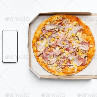Pizza in box and smartphone with blank screen on white table