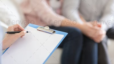 Psychotherapist writing in blank notepad at therapy session