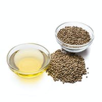 Hemp oil and seeds in bowls on white