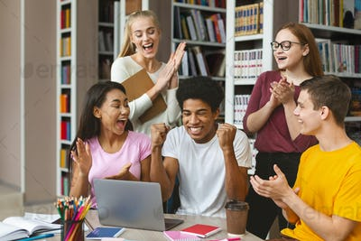 Group of young euphoric students enjoying test results in library