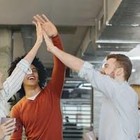 Multiracial millennial friends giving high five in office