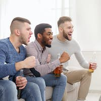Diverse friends cheering for favourite team at home