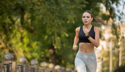 Motivated millennial woman running forward to goal