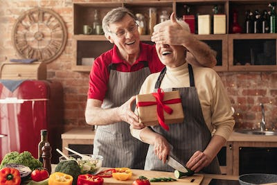 Senior woman receiving gift from her loving husband in kitchen