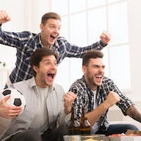 Football fans. Friends cheering for favourite team at home