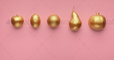 Golden fruits in row on pink