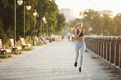 Beautiful female athlete running in park during everyday practice