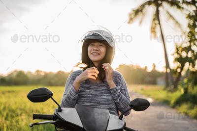 woman wearing and fasten her helmet while riding