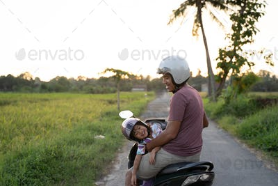 fahter and his child enjoy riding motorcycle scooter