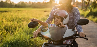 mom and child enjoy riding motorcycle scooter