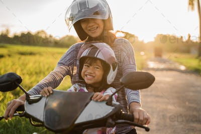 mom and her child enjoy riding motorcycle scooter