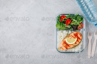 Meal prep containers with salmon and rice, green mix salad with tomatoes.