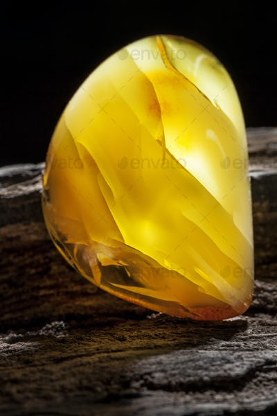 Natural amber. A piece of yellow opaque natural amber on large piece of dark stoned wood