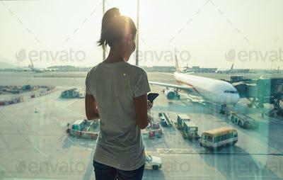 Woman passenger using mobile phone in airport