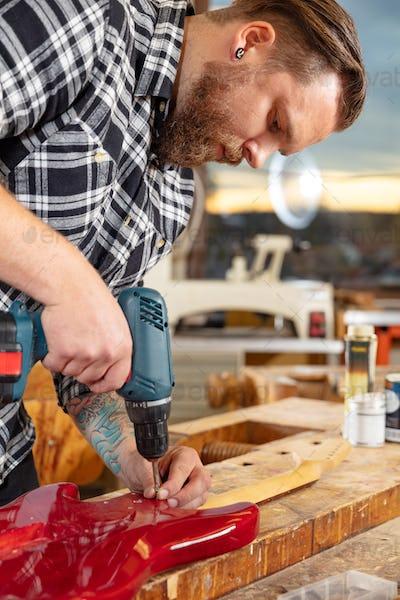 Portrait of craftsman working in workshop with guitar