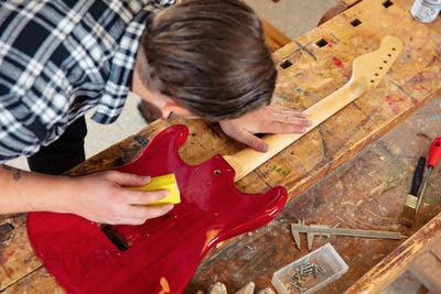 Top view of craftsman sanding a guitar neck in wood at workshop