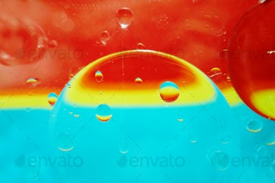 A beautiful and vibrant macro of oil bubbles on water with a yel