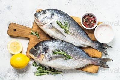 Raw dorado fish on cutting board on the table