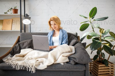 Young woman under a blanket using laptop on couch
