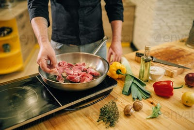 Male person cooking meat with herbs in a pan