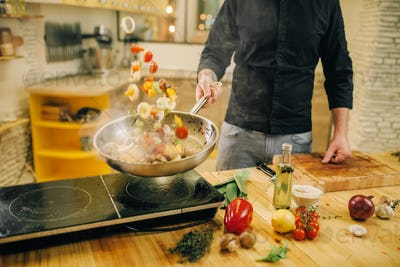 Male chef cooking meat with vetables into the pan