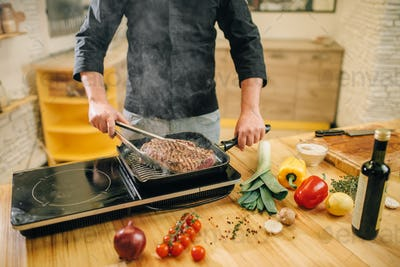 Male person cooking meat in a pan on the kitchen