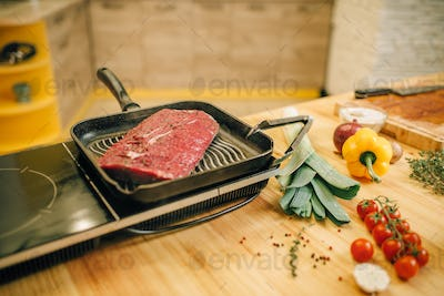 Roasted meat in a frying pan on electric stove
